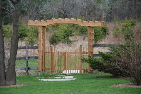 An gate under an arbour makes a beautiful entrance in Cambridge, by Great Lakes Landscape